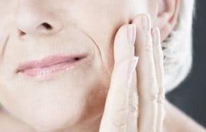 Mujer mayor tocándose la mejilla izquierda con la mano