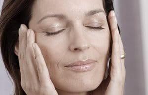 Mujer de mediana edad sujetándose la cara con ambas manos.