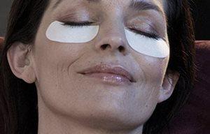 Cara femenina con gasas para el cuidado de los párpados inferiores.